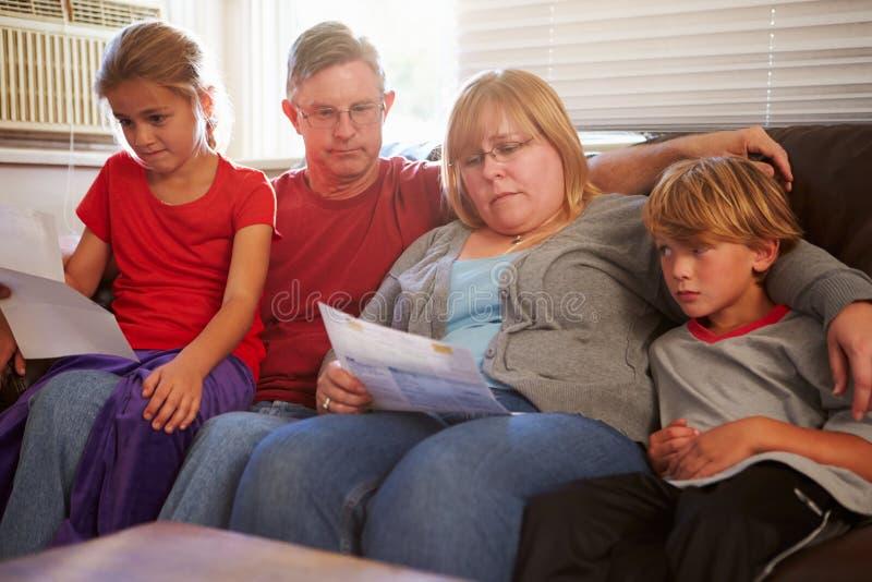 Unglückliche Familie, die auf Sofa Looking At Bills sitzt lizenzfreie stockfotos