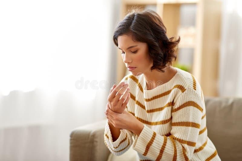 Unglückliche Frau, die in der Hand unter den Schmerz zu Hause leidet lizenzfreie stockbilder