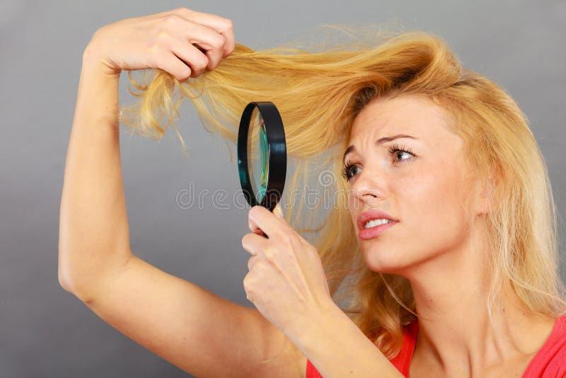 Unglückliche Frau, die durch Vergrößerungsglas zerstörtes Haar schaut stockbild
