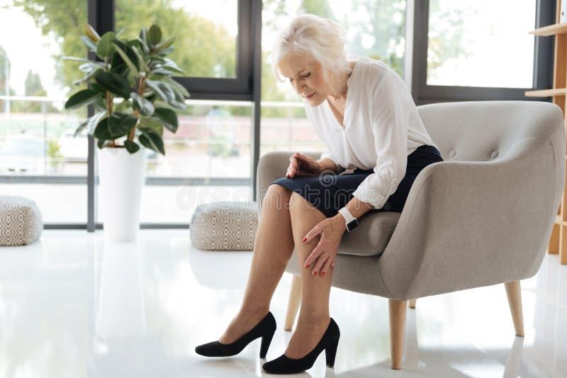 Unglückliche freudlose Frau, die ihre Beine betrachtet stockbild