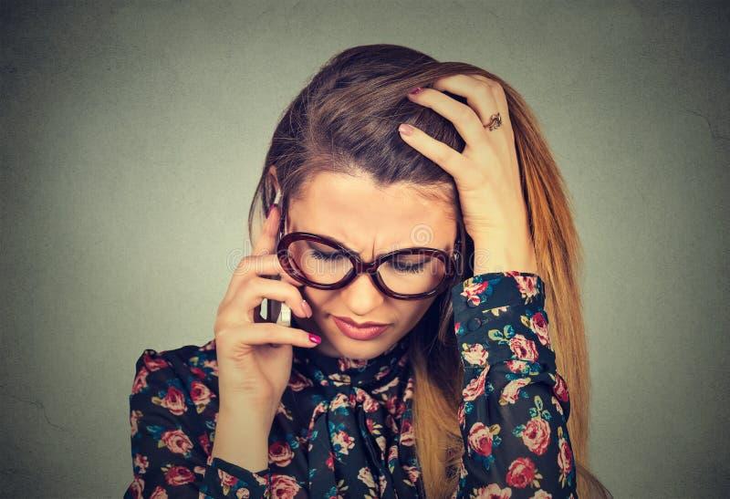 Unglückliche hoffnungslose junge Frau, die am Handy unten schaut spricht stockfotografie