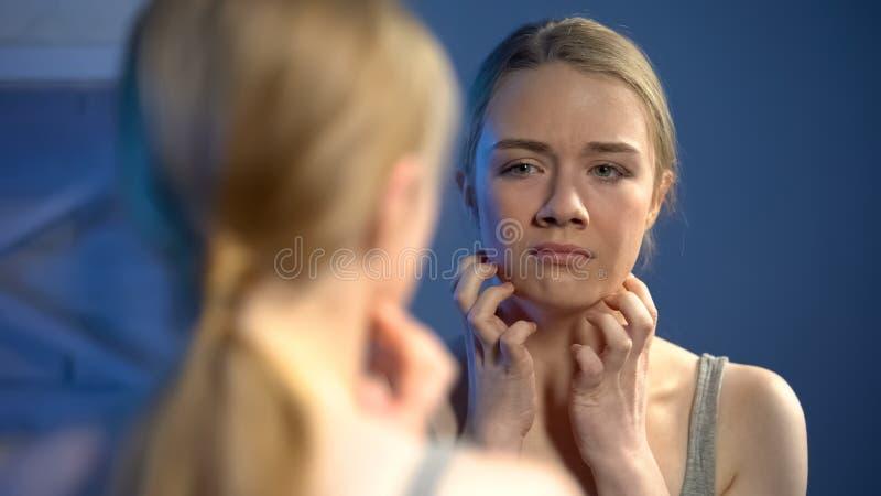 Unglückliche junge Dame, die in der Spiegelreflexion, Umkippen mit Hautunvollkommenheit schaut stockfotografie