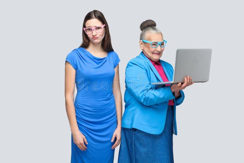Unglückliche junge Frau, die nahe Arbeits-COM der älteren Frau des Glückes steht lizenzfreie stockfotografie