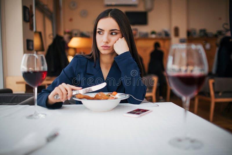 Unglückliche junge Frau sitzen bei Tisch im Restaurant Sie ist allein Vorbildliches Griffmesser in der Hand Zwei Gläser des Rotwe lizenzfreie stockbilder