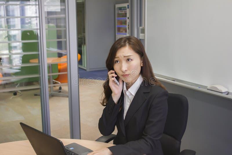 Unglückliche junge Geschäftsfrau, die mit einem Handy spricht stockfotografie