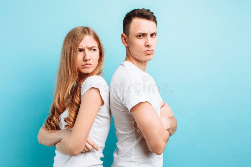 Unglückliche junge Paare, Mann und Frau stehen mit ihren Rückseiten miteinander und betrachten einander mit den gekreuzten Armen lizenzfreie stockbilder