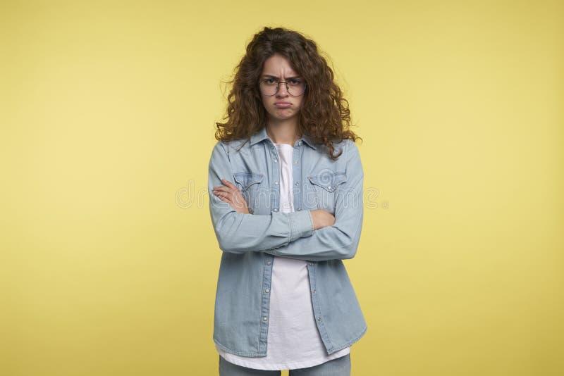 Unglückliche lustige Brunettefrau mit dem gelockten Haar, über gelbem Hintergrund lizenzfreie stockfotografie