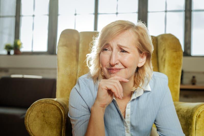 Unglückliche missverstandene Frau, die sonderbares Gesicht beim Sitzen hat lizenzfreie stockfotografie