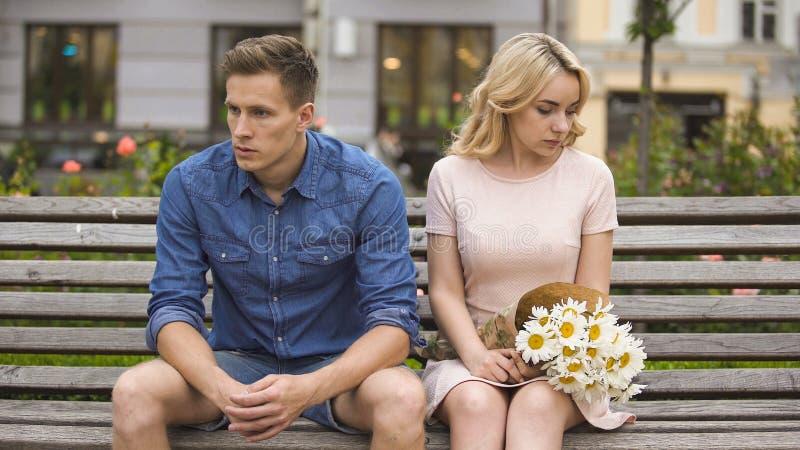 Unglückliche Paare, die nach Kampf, Mädchen mit Blumen, Problem im Verhältnis sitzen lizenzfreies stockbild