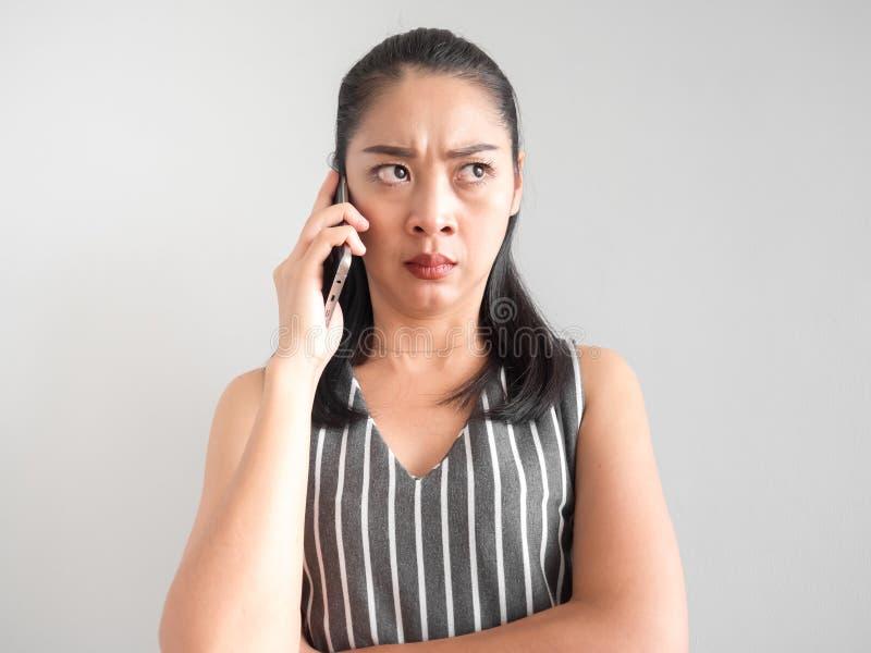 Unglückliche und verärgerte Frau, die auf Smartphone spricht lizenzfreie stockbilder