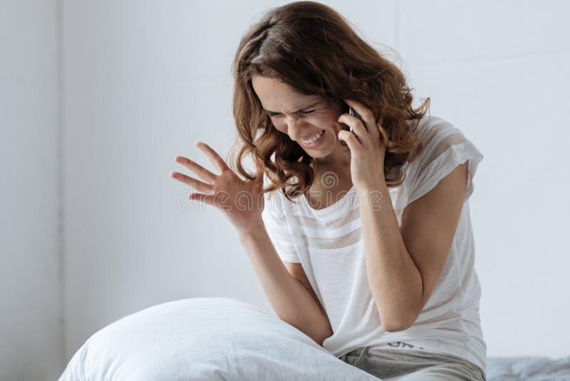Unglückliche verärgerte Frau, die am Telefon spricht stockfoto