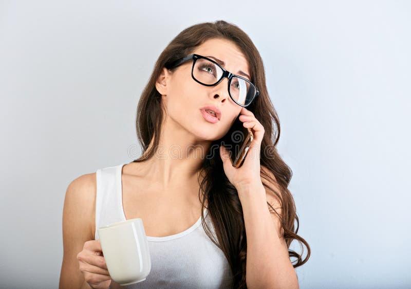 Unglückliche verärgerte Schönheit, die am Handy in den Brillen spricht und Tasse Kaffee auf blauem Hintergrund mit leerer Kopie h stockfotografie