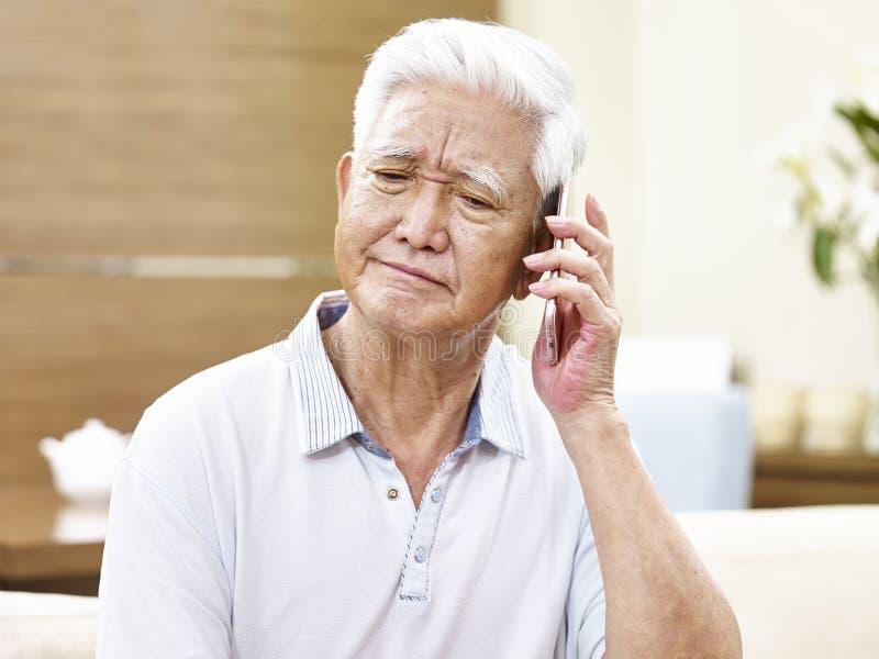 Unglücklicher älterer asiatischer Mann, der am Telefon spricht stockfotografie