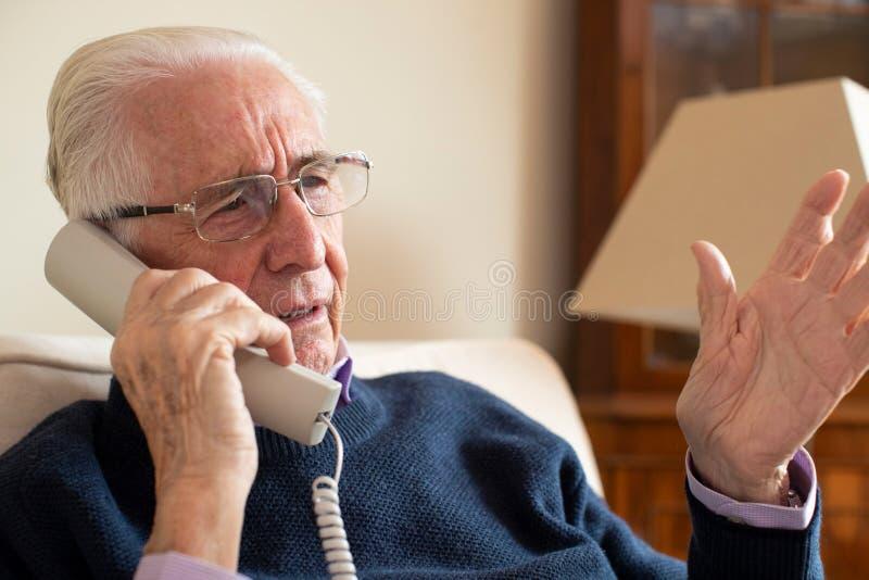 Unglücklicher älterer Mann, der zu Hause unerwünschten Telefonanruf empfängt stockfoto