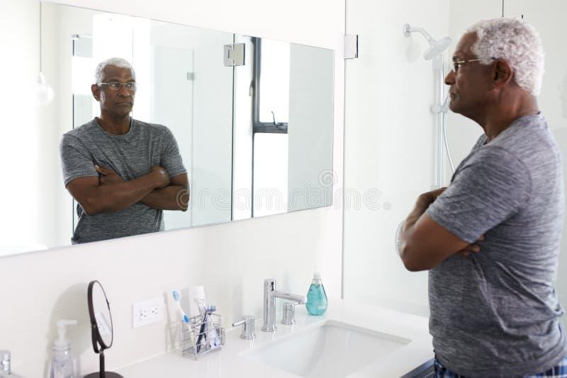 Unglücklicher deprimierter älterer Mann, der Reflexion im Badezimmer-Spiegel betrachtet stockfotos