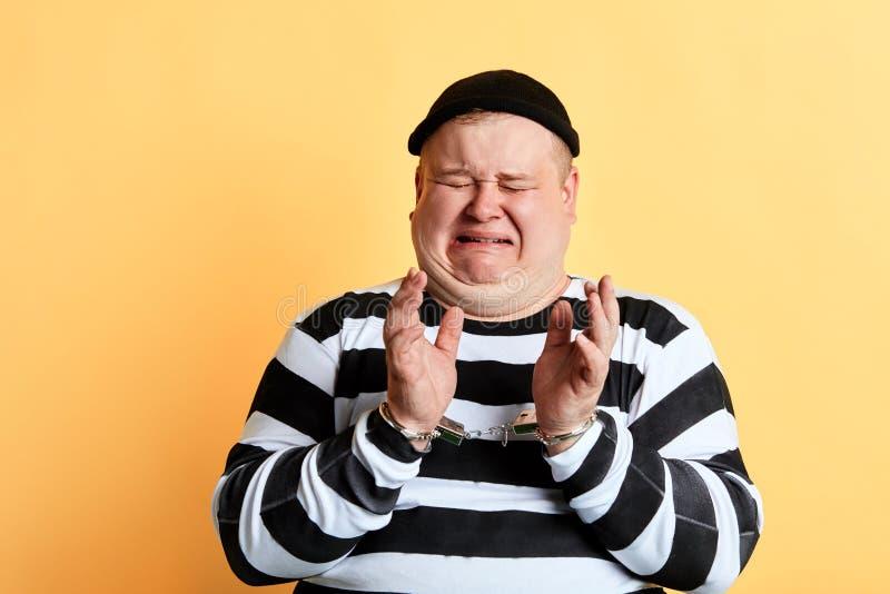 Unglücklicher Dieb mit der Handschelle schreit stockfotografie