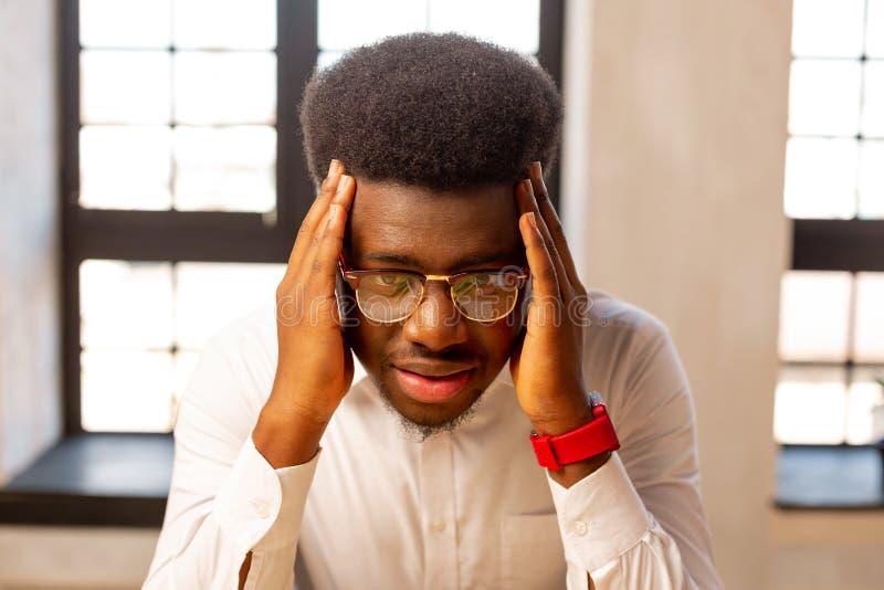 Unglücklicher freudloser junger Mann, der seinen Kopf hält lizenzfreies stockfoto