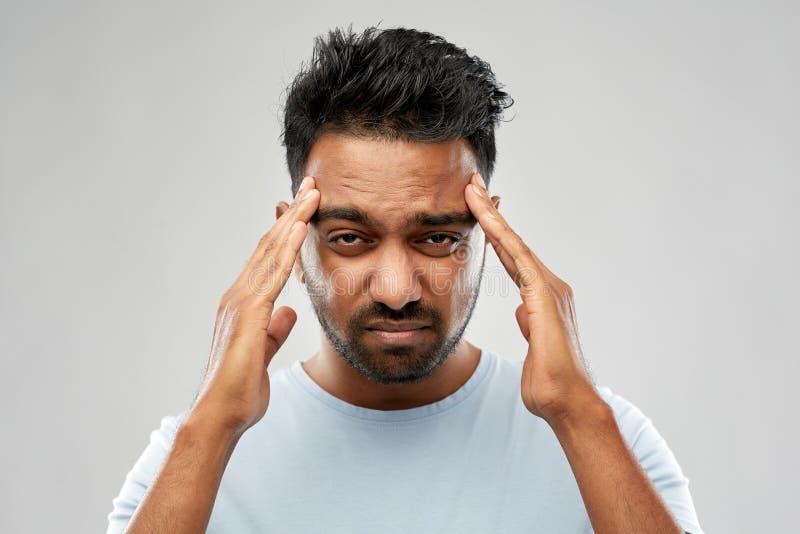 Unglücklicher indischer Mann, der unter Kopfschmerzen leidet lizenzfreies stockfoto