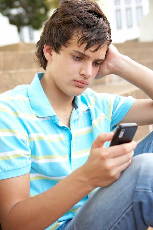 Unglücklicher Jugendkursteilnehmer draußen unter Verwendung des Handys lizenzfreie stockfotos
