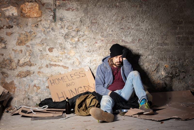 Unglücklicher Mann, der auf dem Boden mit Almosenkorb sitzt lizenzfreie stockbilder