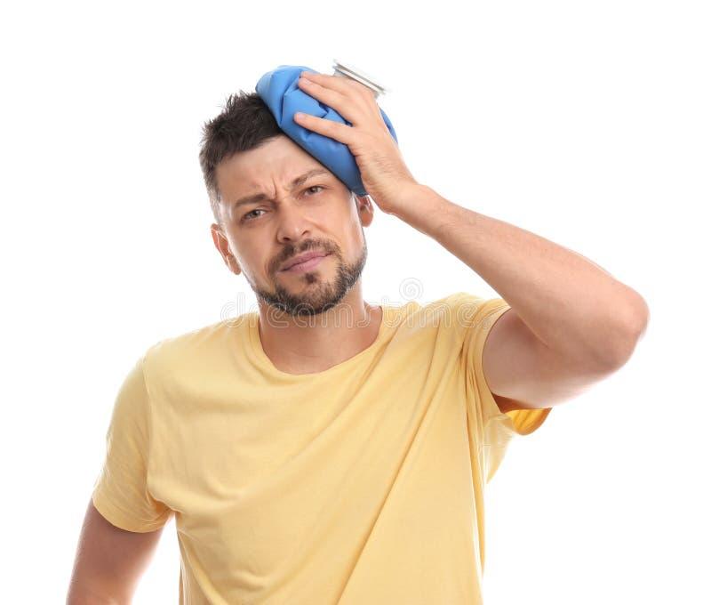 Unglücklicher Mann mit kalter Packung zur Heilung von Kopfschmerzen auf weiß lizenzfreie stockfotografie