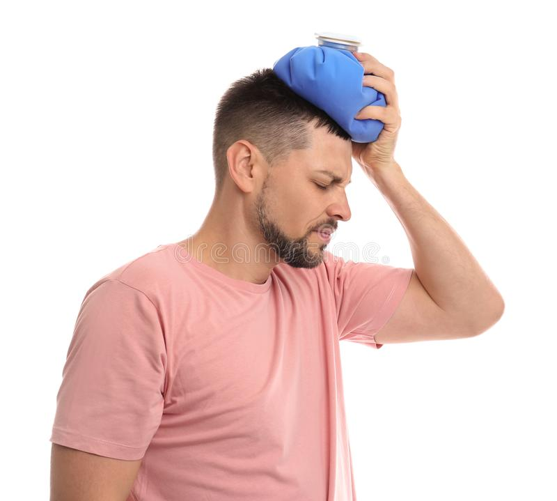 Unglücklicher Mann mit Kaltpackung zur Heilung von Kopfschmerzen im Hintergrund lizenzfreies stockbild