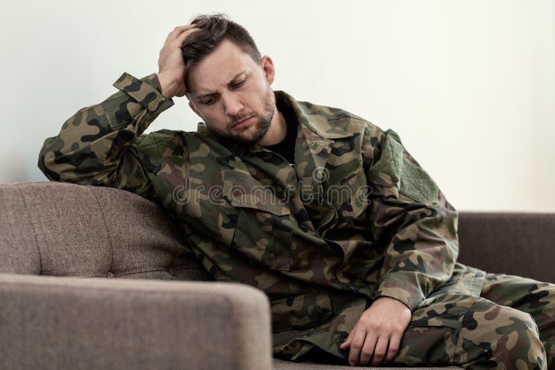 Unglücklicher und trauriger Soldat in grüner Moro-Uniform mit Kriegssyndrom stockbild