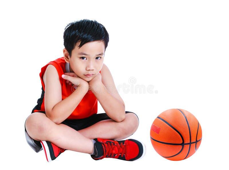 Unglückliches asiatisches Kind, das nahe Basketball sitzt lokalisiert auf weißem b stockfoto