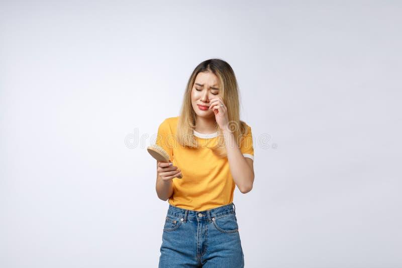Unglückliches asiatisches Mädchen am Telefon, Unterhaltungstelefon der verärgerten Asiatin mit ihrem Freund, lokalisiert auf weiß stockfotografie