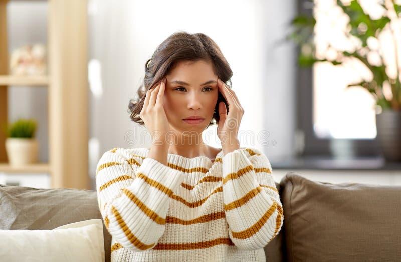 Unglückliches Frauenleiden vom Hauptschmerz zu Hause lizenzfreie stockfotos