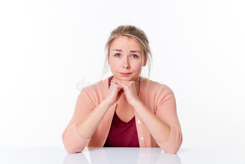 Unglückliches junges blondes Frauensitzen, tut mir leid entschuldigend und glauben lizenzfreie stockbilder