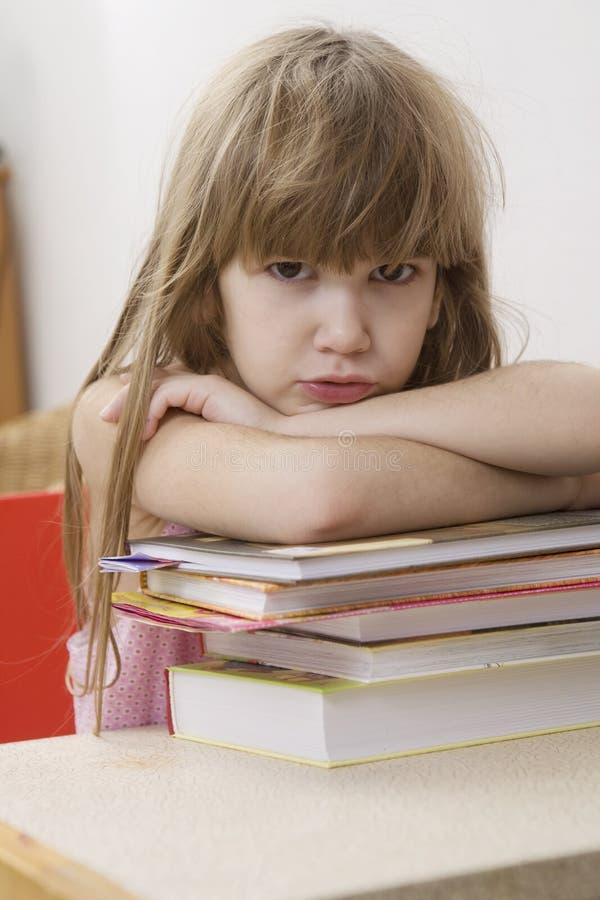 Unglückliches kleines Mädchen, das am Schreibtisch sitzt lizenzfreie stockfotografie