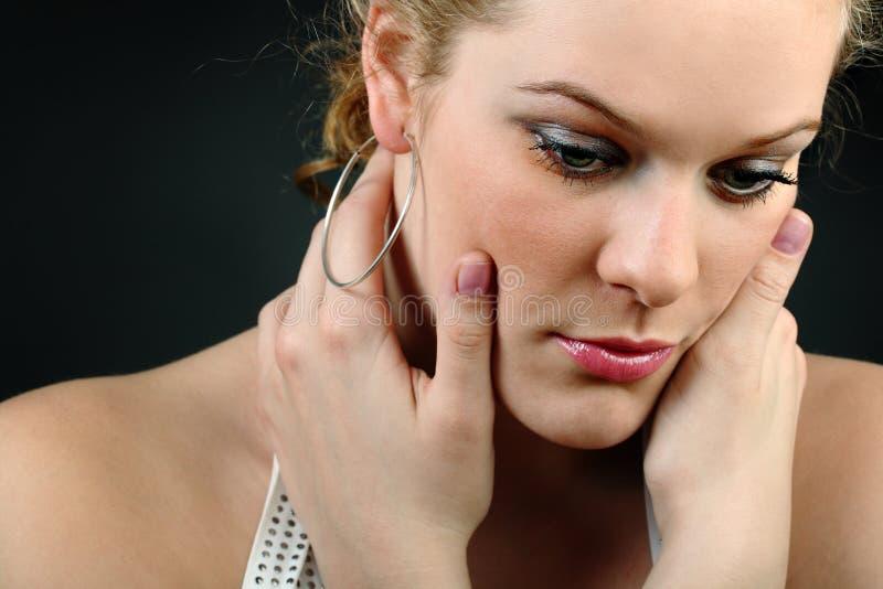 Unglückliches Mädchen, das ihr Gesicht auf schwarzem Hintergrund berührt lizenzfreie stockfotos