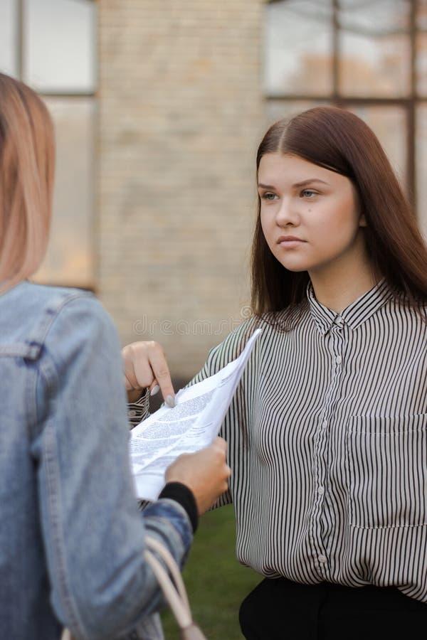 Unglückliches Mädchen steht nahe der Universität und den Punkten, um zu tapezieren stockbilder