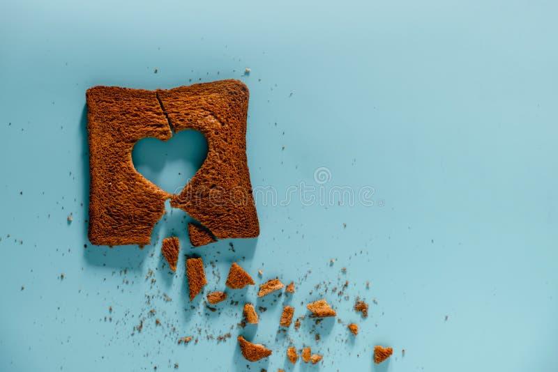 Unglückliches Verhältnis-Konzept Flache Lage von gebrannt schnitt Toastbrot mit einer Form des defekten Herzens lizenzfreies stockfoto