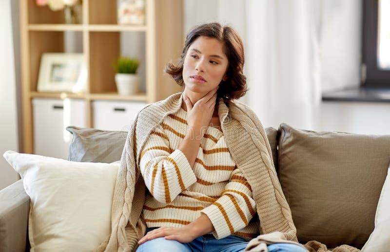 Ungl?ckliche kranke Frau mit den Halsschmerzen zu Hause stockfotos