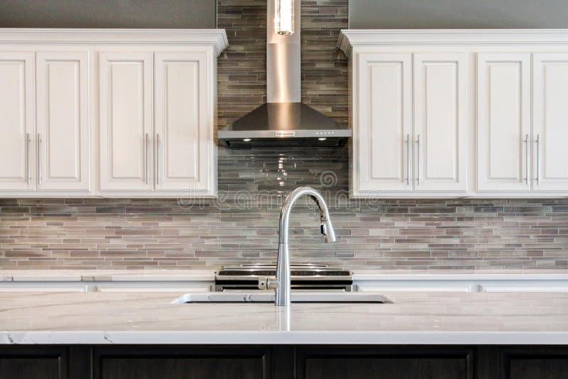 Unglaubliche zeitgenössische Küche mit weißen Kabinetten und Glas-backsplash lizenzfreie stockfotos