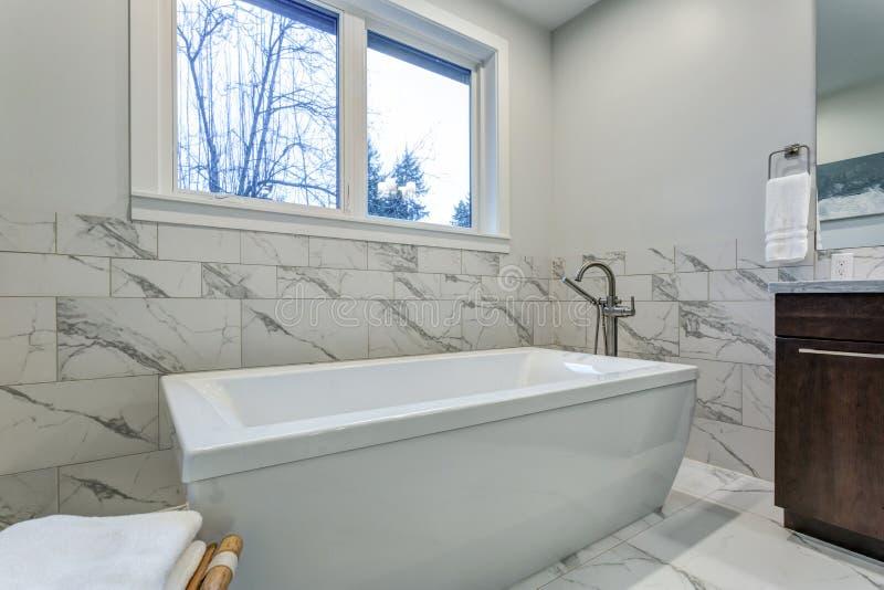 Unglaubliches Vorlagenbadezimmer mit Carrara-Marmorflieseneinfassung stockfoto
