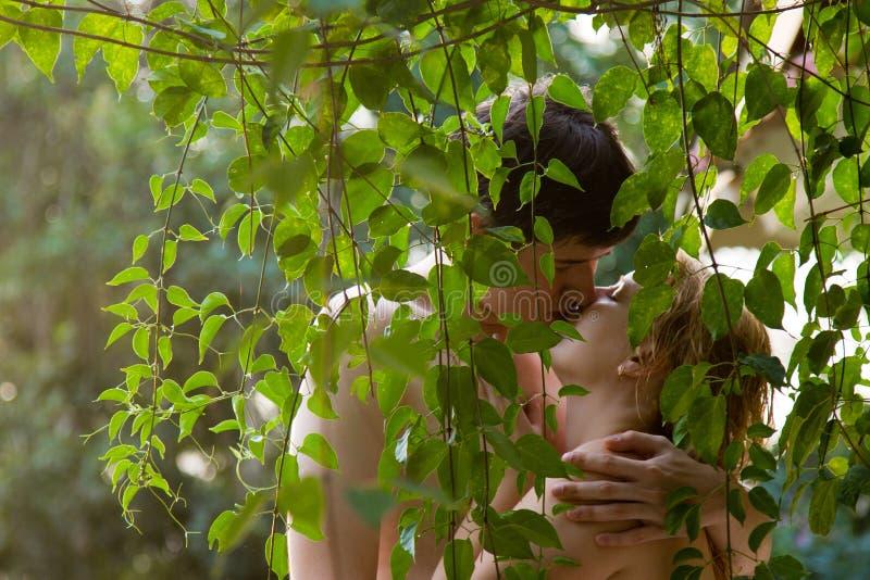 Ungt älskvärt kyssa för par som är naket i trädgård arkivbilder