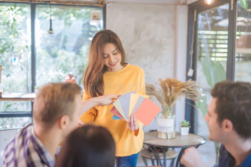 Ungt affärsfolk och lagformgivare som arbetar med färgpaletten Asiatisk modell som väljer färgprovtagningen på nytt projekt arkivbild