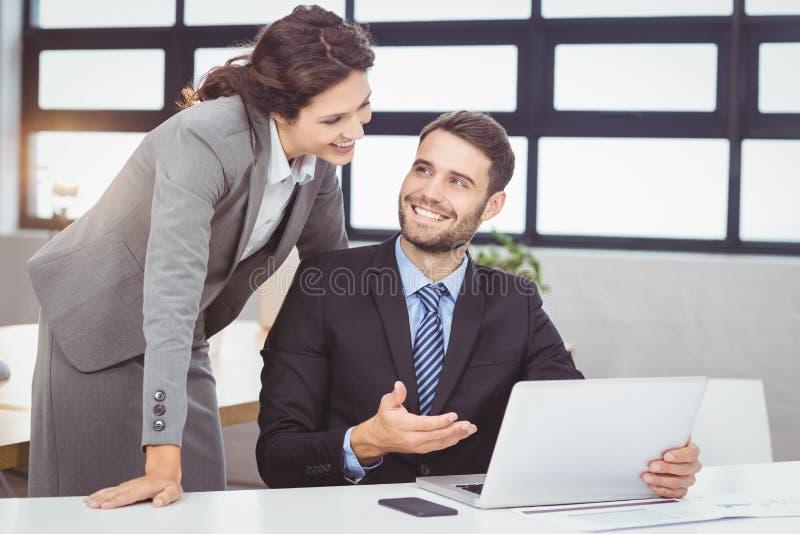 Ungt affärsfolk som diskuterar över bärbara datorn royaltyfria bilder