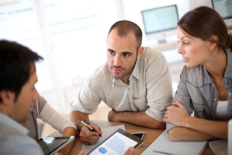 Ungt affärsfolk som diskuterar strategi arkivbild