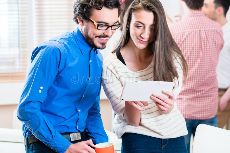 Ungt affärsfolk som ser minnestavlaPC arkivbild