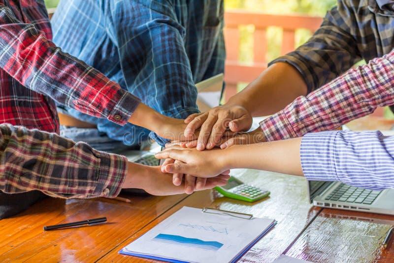 Ungt affärsfolk som tillsammans sätter deras händer Bunt av han arkivfoto