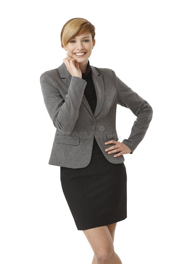 Ungt affärskvinnaanseende med handen på höft arkivfoto