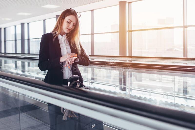 Ungt affärskvinnaanseende på rullbandstrottoaren och se hennes armbandsur i flygplats royaltyfria bilder