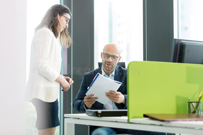 Download Ungt Affärskvinnaanseende Vid Affärsmanläseboken På Kontoret Fotografering för Bildbyråer - Bild av kontor, män: 78728203