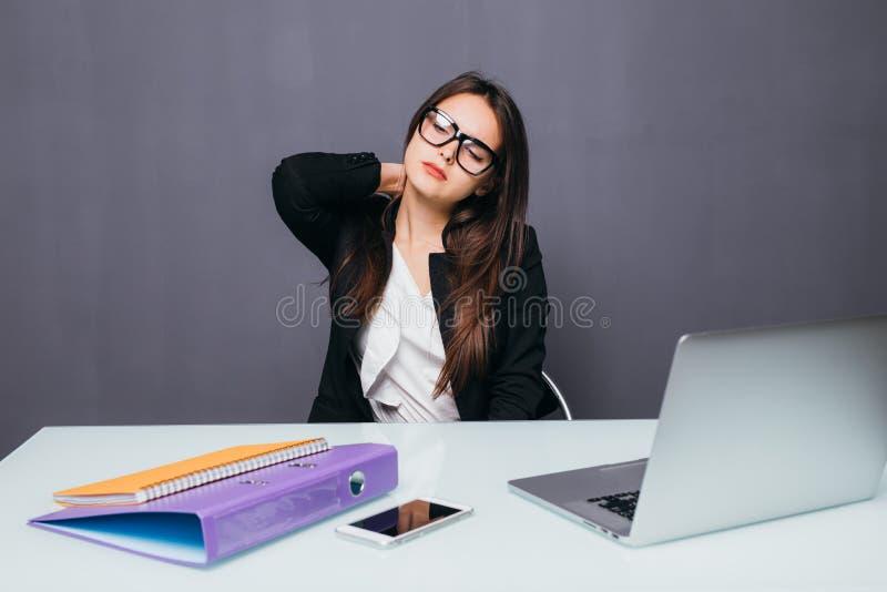 Ungt affärskvinnalidande från hals smärtar på kontorsskrivbordet royaltyfria foton