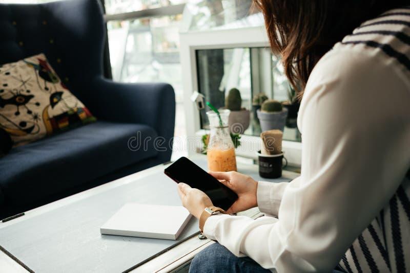 Ungt affärskvinnasammanträde i arbetsplats och användamobiltelefon arkivfoto