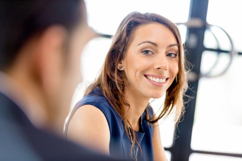Ungt affärskvinnasammanträde på skrivbordet och arbete arkivfoton